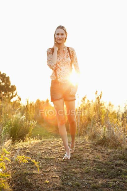 Впевнена в собі жінка йде по сліду в сільській місцевості і посміхаються — стокове фото