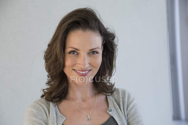 Portrait of happy mature woman on grey background — Stock Photo