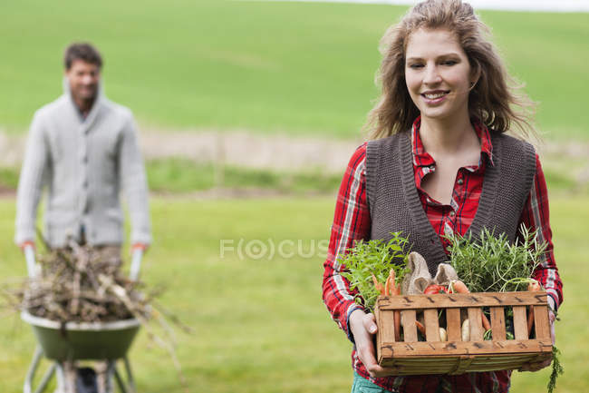 Woman holding basket of vegetables with husband collecting firewood in countryside — Stock Photo
