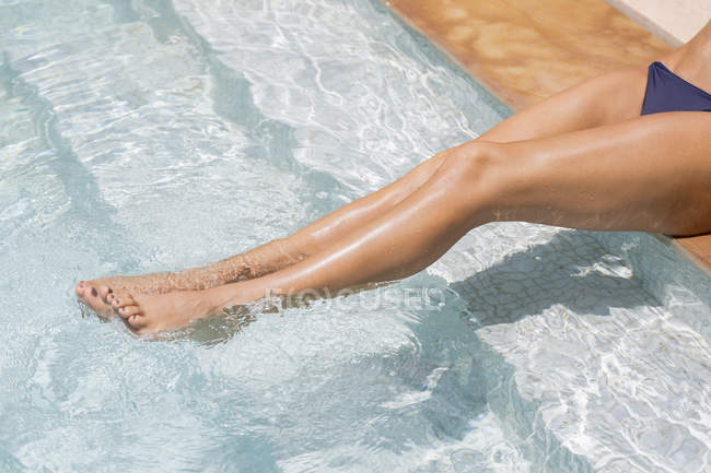 Slim legs of woman relaxing at poolside — Stock Photo