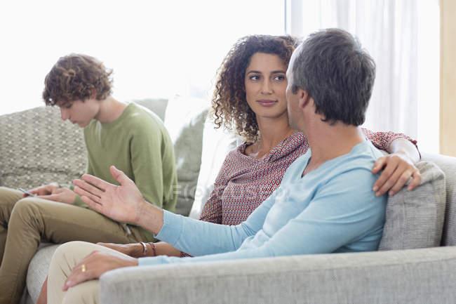 Pareja sentada en el sofá y hablar con el hijo mediante el teléfono móvil en el fondo en la sala de estar en casa - foto de stock