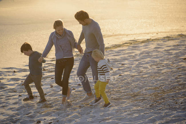 Счастливая семья гуляет по пляжу на закате — стоковое фото
