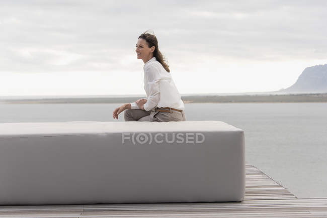 Happy mature woman sitting on ottoman at lake shore and looking away — Stock Photo