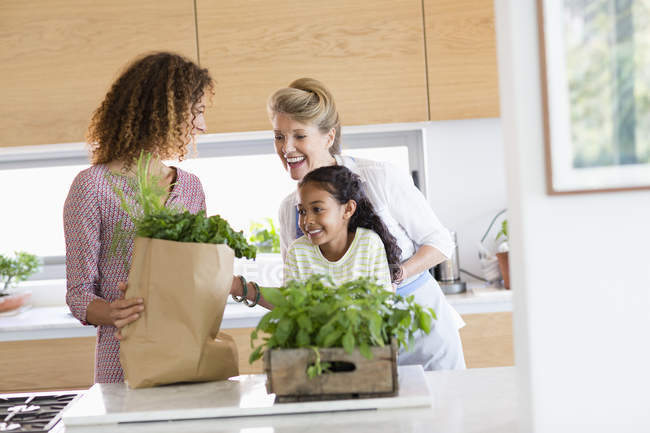 Senior woman with daughter and granddaughter looking at greens in kitchen — Stock Photo