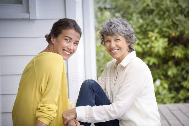 Portrait of happy mother sitting with adult daughter on porch — Stock Photo