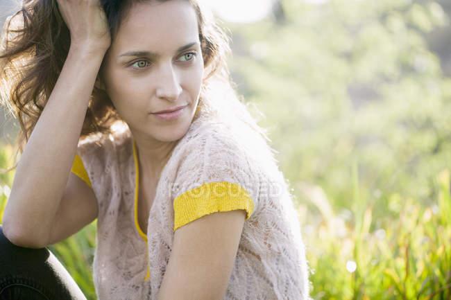 Donna sognante seduta nell'erba soleggiata — Foto stock