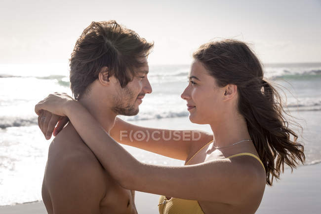 Smiling young couple embracing on sunny beach — Stock Photo