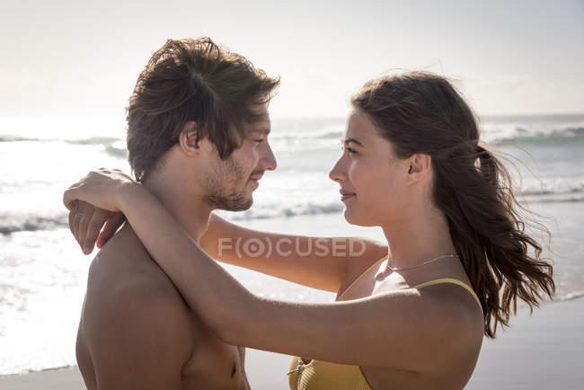 Lächelnd junges Paar umarmt am Sonnenstrand — Stockfoto