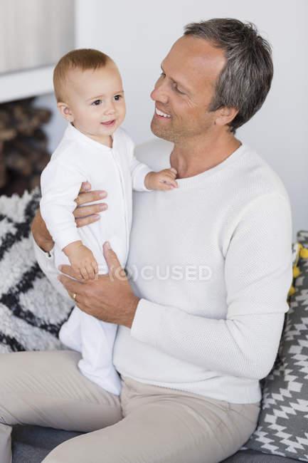 Щасливий батько сидить на дивані і граючи з милий дитина дочка у вітальні — стокове фото