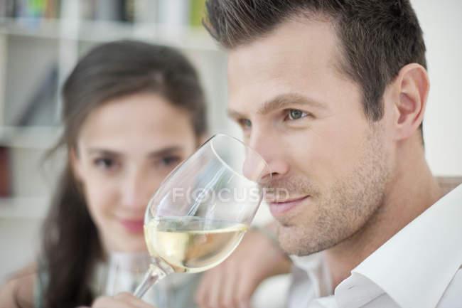 Uomo bere vino bianco con moglie su sfondo — Foto stock