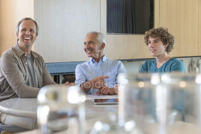 Hombre senior feliz con hijo y su nieto sentado y hablando a la mesa en la sala de estar - foto de stock