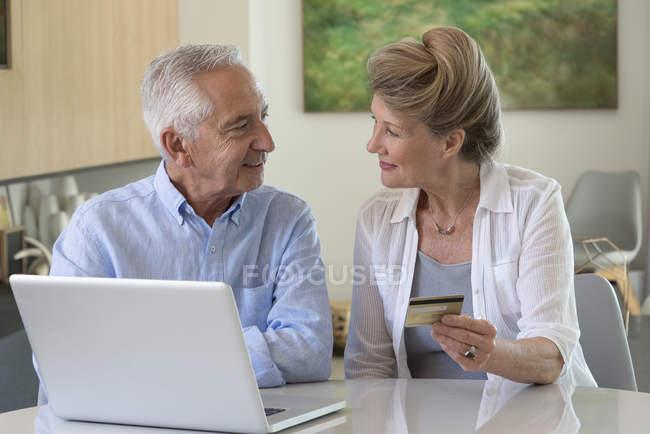 Coppia senior shopping online con laptop a casa — Foto stock