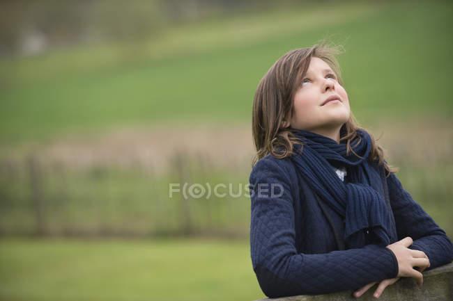 Teenage girl looking up on green field — Foto stock