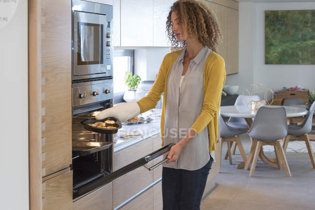 Woman putting dish of food into oven in kitchen — Stock Photo