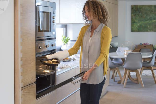 Donna che mette il piatto di cibo nel forno in cucina — Foto stock