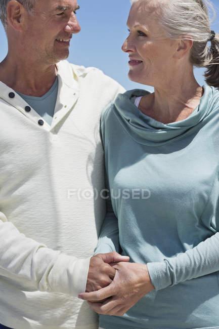 Pareja senior romántica mirando el uno al otro al aire libre - foto de stock