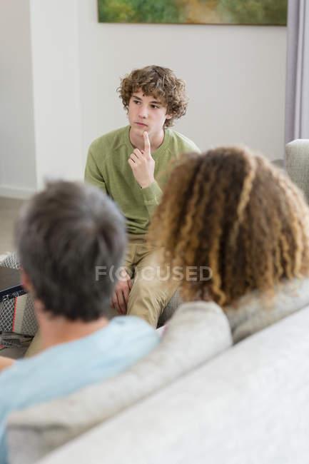 Мальчик, говорить родителям, сидя на диване в гостиной в доме — стоковое фото