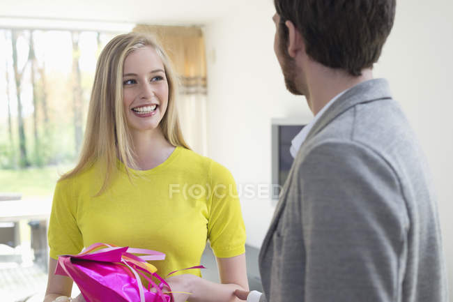 Smiling young woman receiving gift from boyfriend at home — стокове фото