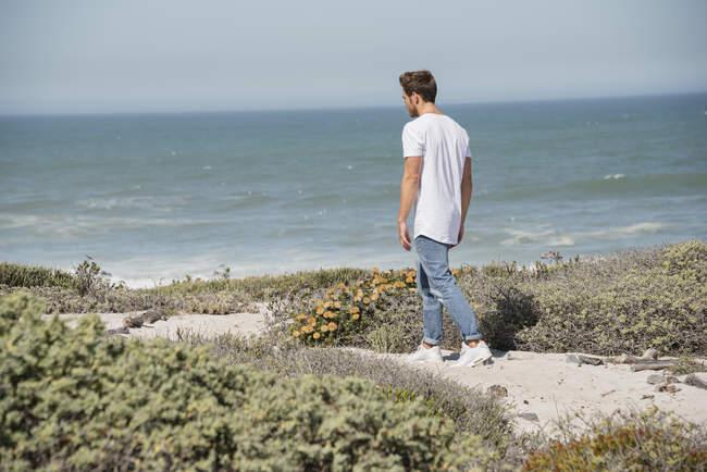 Молода людина, ходьба на узбережжі моря — стокове фото