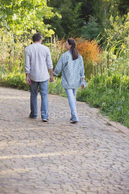 Blick von hinten auf reifes Paar, das in sonnigem Garten spaziert — Stockfoto