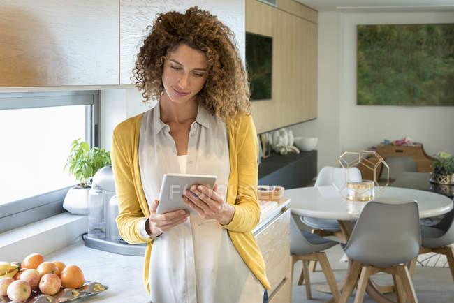 Woman using digital table in modern kitchen — Stock Photo