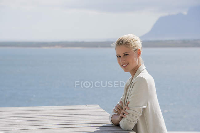 Portrait of smiling elegant young woman sitting at table on lake shore — Stock Photo