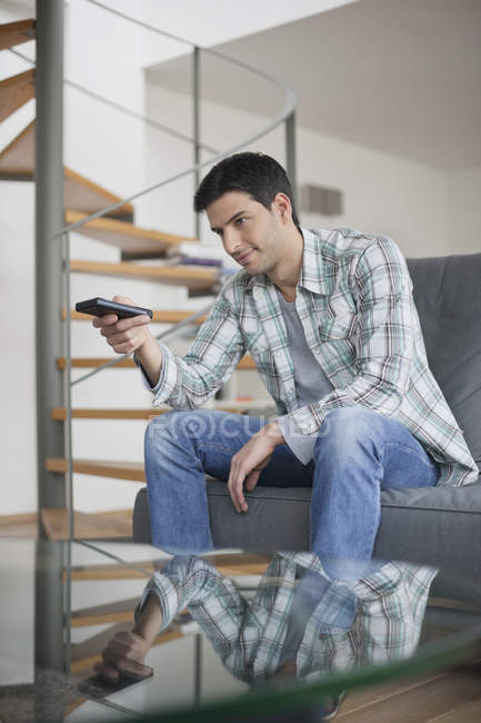 Homme, changer de chaîne avec la télécommande sur le canapé — Photo de stock