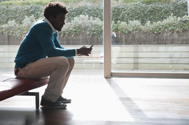Человек текстовых сообщений с мобильного телефона на скамейке в номере — стоковое фото