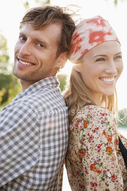 Side view of smiling couple standing back to back and looking at camera — Stock Photo