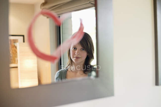 Adolescente que olha a reflexão no espelho decorado com forma do coração — Fotografia de Stock