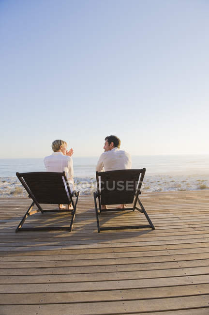 Couple sitting on deck chairs on beach and talking — Stock Photo