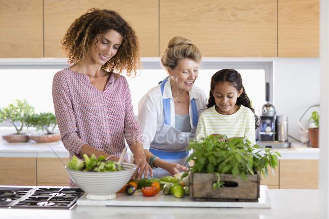 Seniorin mit Tochter und Enkelin bereitet Essen in Küche zu — Stockfoto