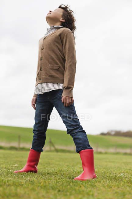 Junge träumt im grünen Feld unter bewölktem Himmel — Stockfoto