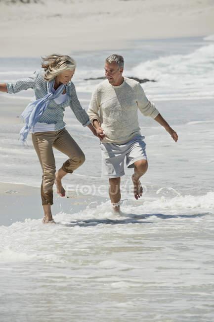 Coppia senior scherzare sulla spiaggia e che tengono le mani — Foto stock