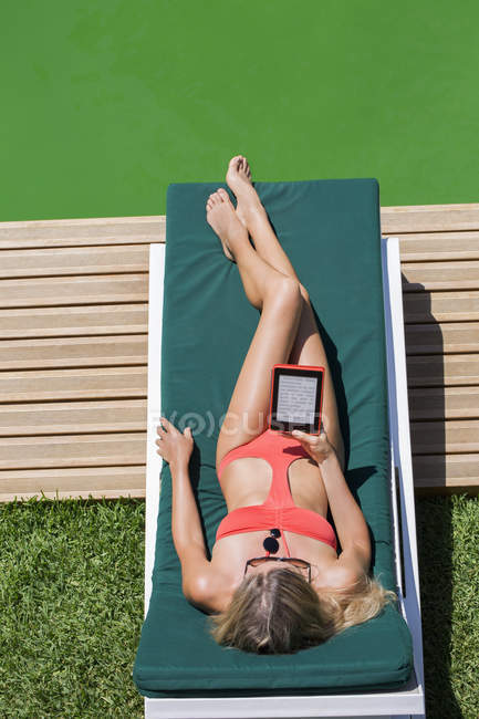 Attractive woman sunbathing and using digital tablet on deckchair — Stock Photo