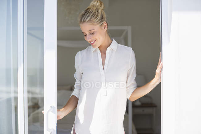 Relaxed young woman with eyes closed standing at window in sunlight — Stock Photo