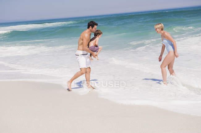 Веселая семья играет на песчаном пляже — стоковое фото