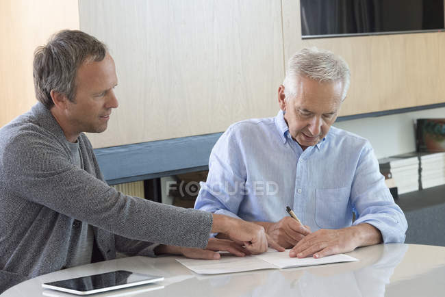 Senior man doing paperwork with financial advisor at home — Stock Photo