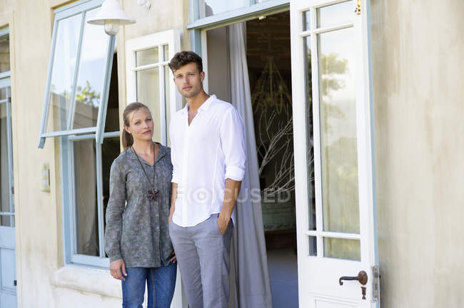 Young couple standing together in front of house — Stock Photo