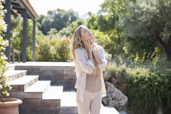 Relaxed woman with eyes closed standing on terrace in garden — Stock Photo