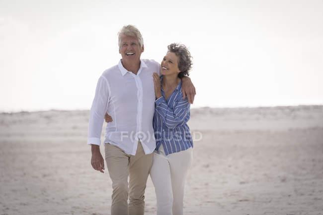 Happy romantic senior couple walking on beach — Stock Photo