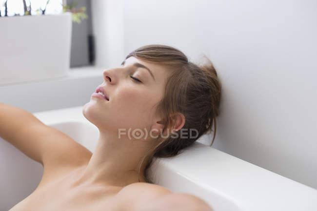 Jovem mulher com os olhos fechados relaxante na banheira — Fotografia de Stock