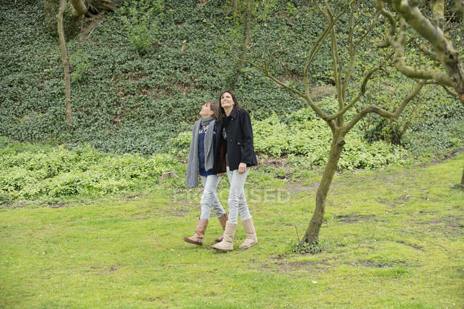 Woman with teenage daughter walking in orchard — Stock Photo