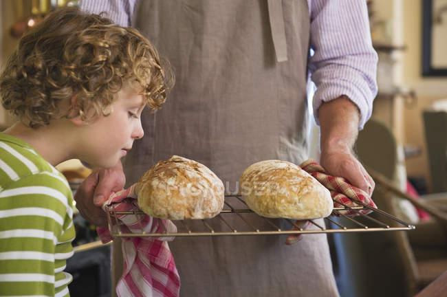 Carino bambino che odora di pane appena sfornato in mani maschili — Foto stock
