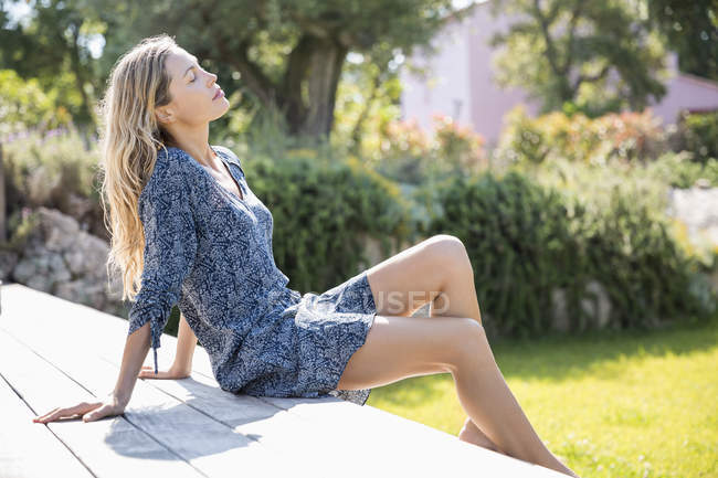 Relaxed slim woman with eyes closed relaxing in garden — Stock Photo