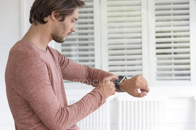 Крупным планом молодого человека, проверяющего умные часы — стоковое фото