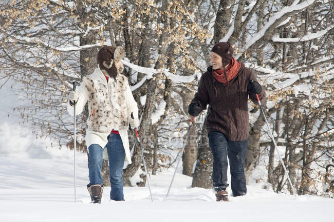 Young couple snowshoeing in winter forest — стокове фото