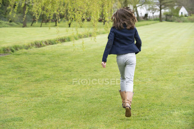 Teenage girl walking on green field — Stock Photo