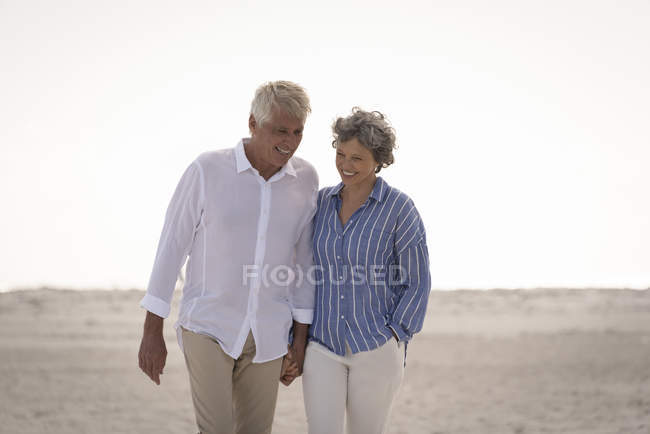 Happy senior couple walking on beach holding hands — Stock Photo
