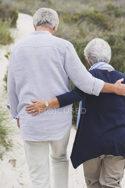 Blick von hinten auf umarmendes Senioren-Paar am Strand — Stockfoto